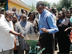 Jean Bosco Musana showing President Kagame the sunflower seed oil production machine