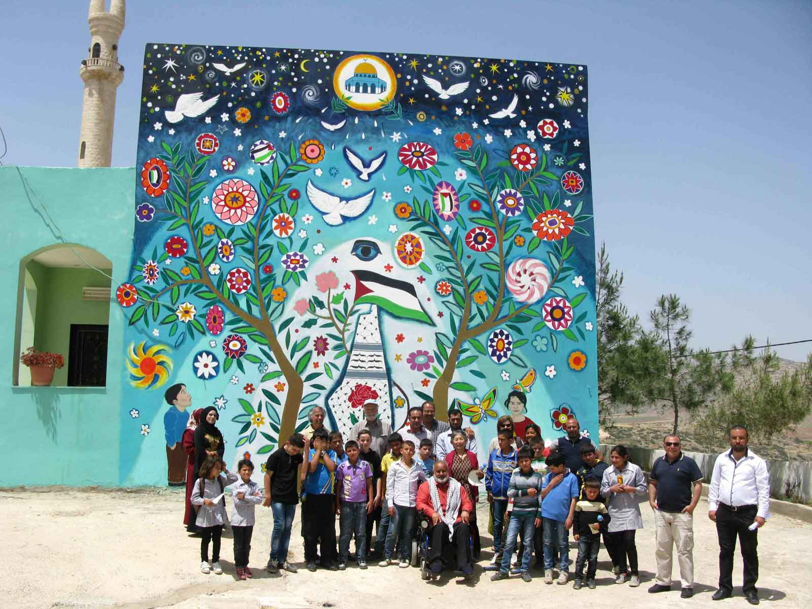 Mayor Haj Sami with his community at the completion of the mural.